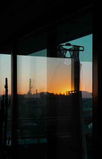 Digital composite image of buildings against sky seen through glass window