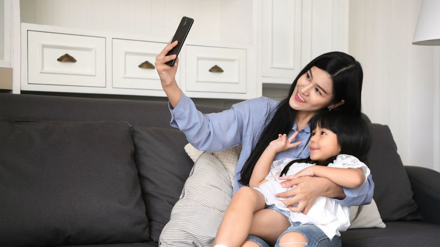 Family concept. Mom is inviting her daughter to take pictures in the living room. Adult ASIA Background Beautiful Casual Caucasian Child Childhood Concept Cute Daughter Expression Face Family Feeling Female Fun Gadget Girl Happiness Happy Hug Japan Leisure Lifestyle Little Look Love Make Mobile Mom Mother Parent People Phone Photo Posing Pretty Selfie Sitting Smart Smile Style Technology Thailand Together Two Using Woman Young