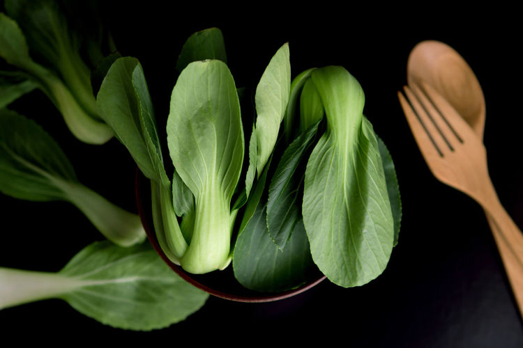 High Angle View Of Leaf Vegetables In Bowl With Wooden Cutleries On Black Background