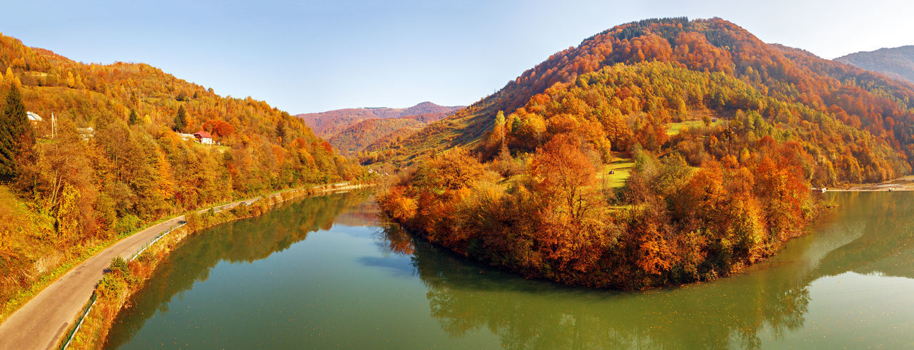 Scenic view of lake by mountain against sky during autumn