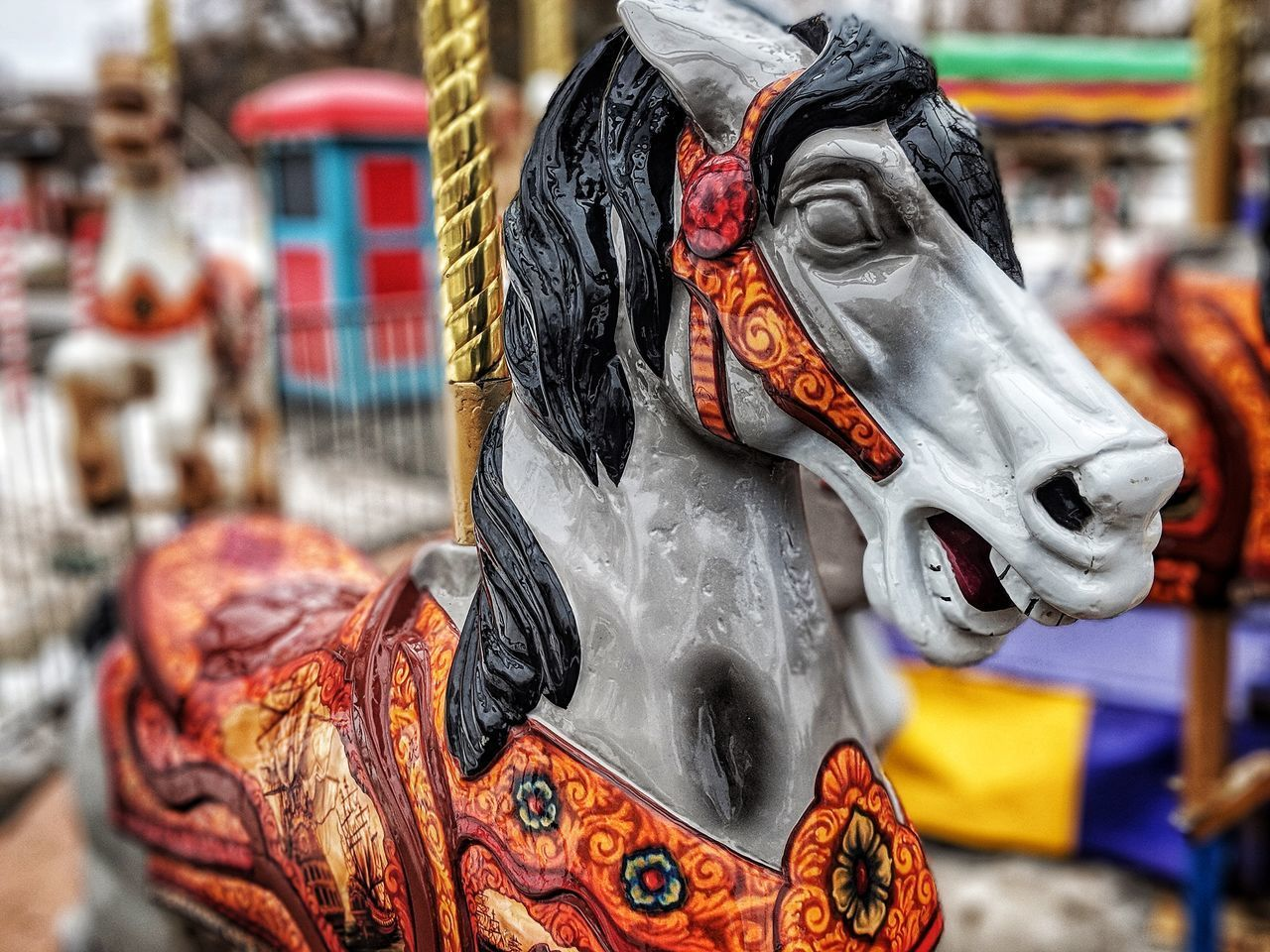 CLOSE-UP OF ANIMAL SCULPTURE ON CAROUSEL IN AMUSEMENT PARK