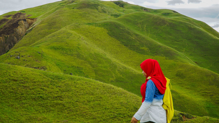 Woman walking on green hill against sky