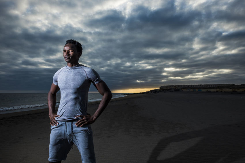 handsome fashion pose for black race handsome boy with artificial light standing on the beach and sunset and beautiful sky in background. abdominal and beauty people athlete in outdoor activity 25-29 Years Beach Beauty In Nature Black Color Casual Clothing Cloud - Sky Front View Jeans Land Leisure Activity Lifestyles Looking At Camera Nature Non-urban Scene One Person Outdoors Real People Sand Scenics - Nature Shore Sky Son Standing Three Quarter Length Young Adult