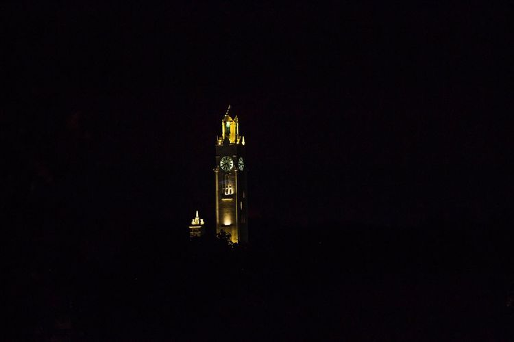 Low angle view of clock tower at night