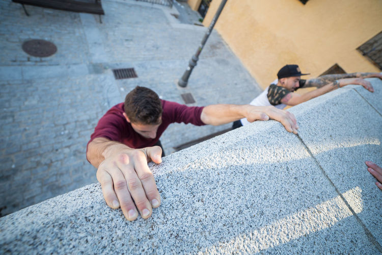 High Angle View Of Male Friends Climbing Wall