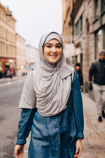 Portrait of smiling young woman standing on city street