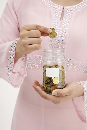 mid section of Malay woman holding a saving jar and coins Business Currency Females Woman Bank Cash Coin Container Deposit Finance Financial Item Front View Holding Investment Midsection Money One Person Profit Saving Jar Savings Tax Unrecognizable Person Wage Wealth Women
