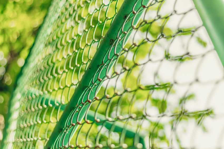 Close up of fence with sunlight through trees and green bokeh background, selective focus. Green Low Angle View Sunlight Tree Abstract Backgrounds Beauty In Nature Blurred Background Bokeh Close Up Close-up Day Design Fence Focus On Foreground Freshness Full Frame Green Color Nature No People Outdoors Pattern Season  Summer Texture