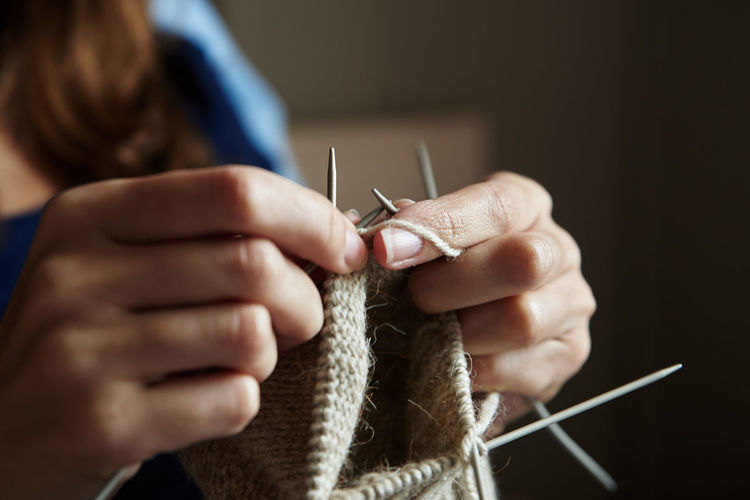 Woman knitting socks with needles