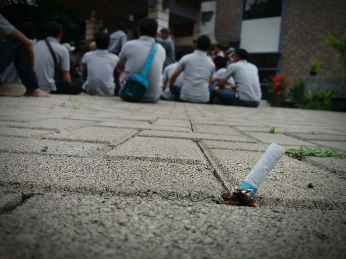 Close-Up Of Cigarette Butt On Footpath