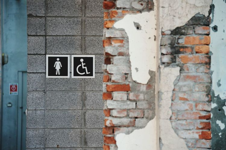 Close-up of restroom signs on wall