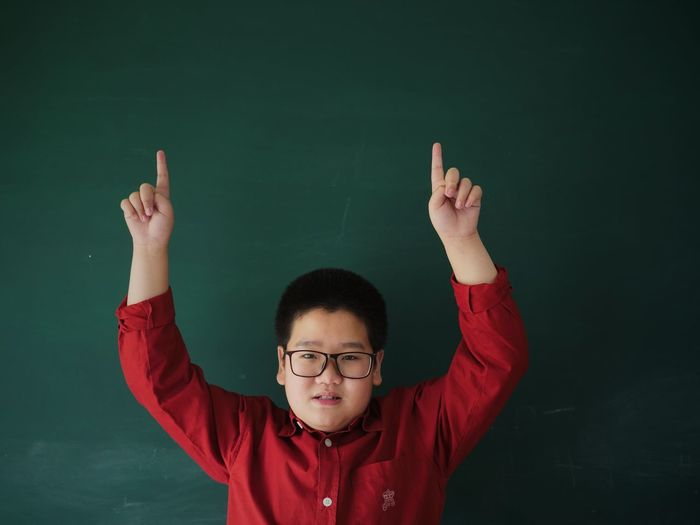 Portrait Of Boy With Arms Raised Standing Against Blackboard In Classroom