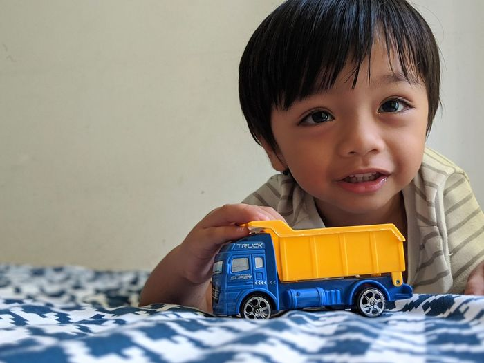 Portrait of cute boy with toy on bed at home