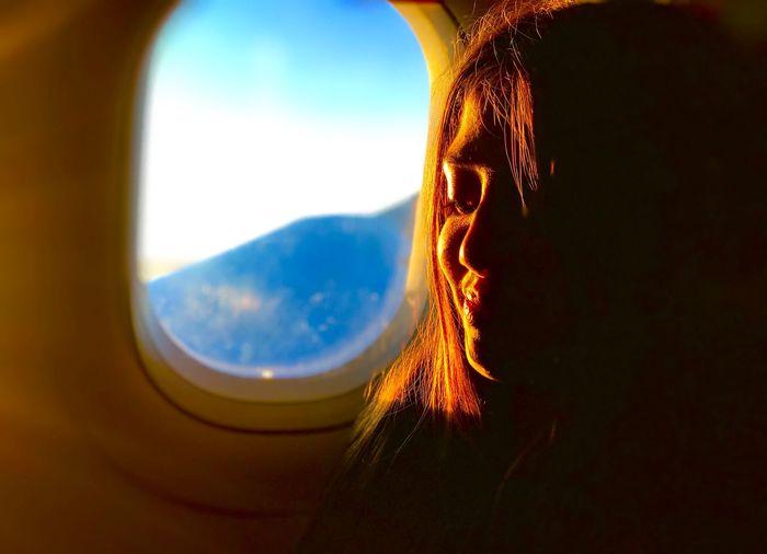 Portrait of woman looking through window