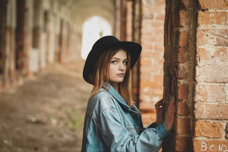 Portrait of beautiful young woman standing against brick wall
