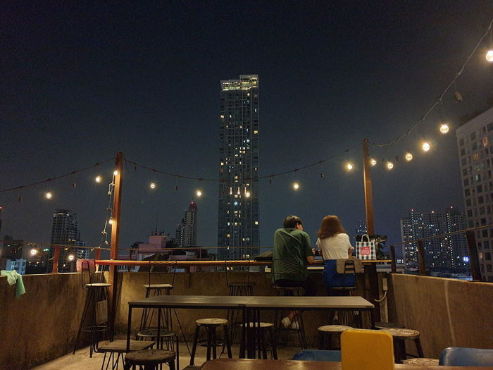 People sitting at illuminated restaurant by buildings against sky at night