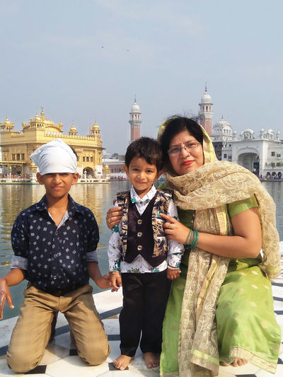 Portrait of happy mother with children on pier against temple amidst lake