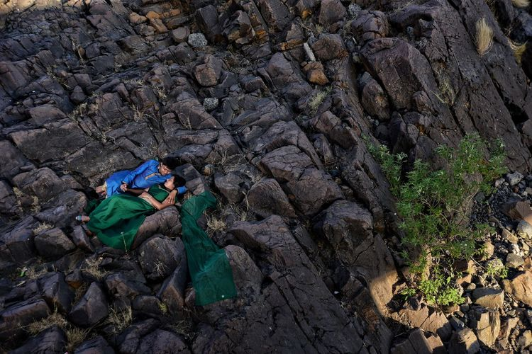 High Angle View Of Young Couple Lying On Rock Formation