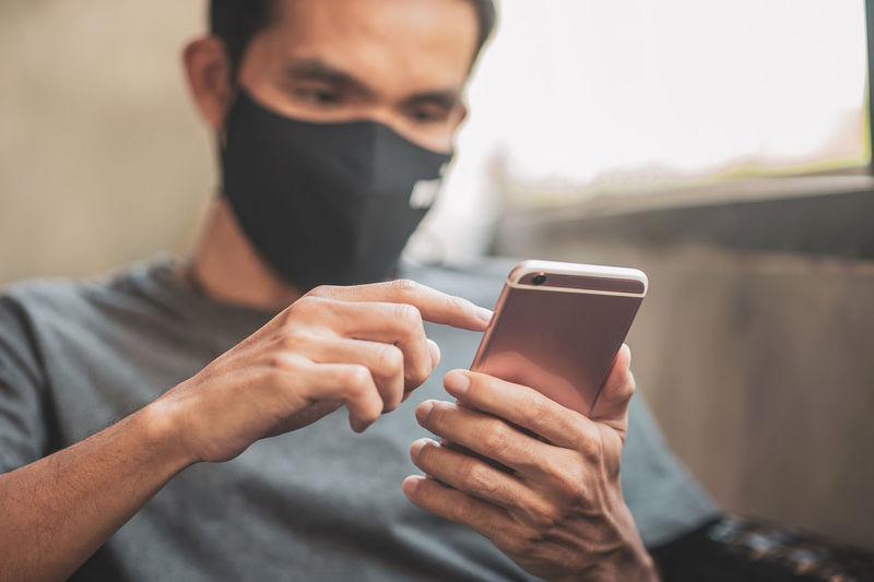 Man wearing mask using smart phone sitting at home