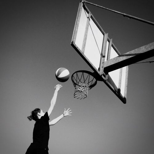 Low Angle View Of Woman Playing Basketball Against Clear Sky