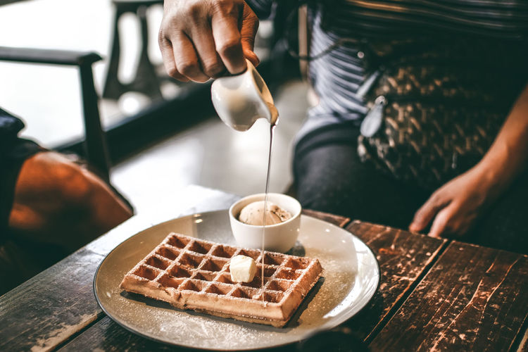 Midsection of man pouring sauce in waffle on table in restaurant