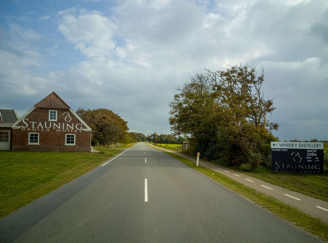 Architecture Building Building Exterior Built Structure Cloud - Sky Day Diminishing Perspective Direction Dividing Line Grass House Nature No People Outdoors Plant Road Road Marking Sign Sky Symbol The Way Forward Transportation Tree
