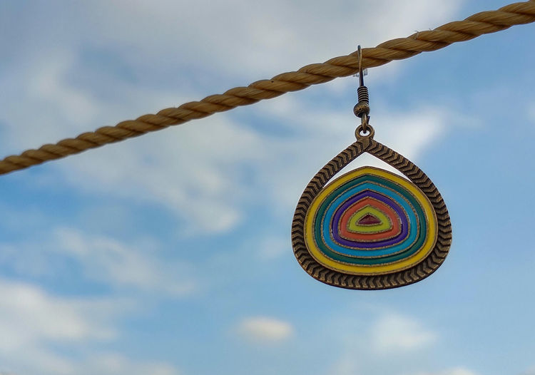 Abstract, delhi, india- low angle view of multi colored earring hanging against sky