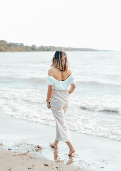 Full length rear view of woman walking on beach
