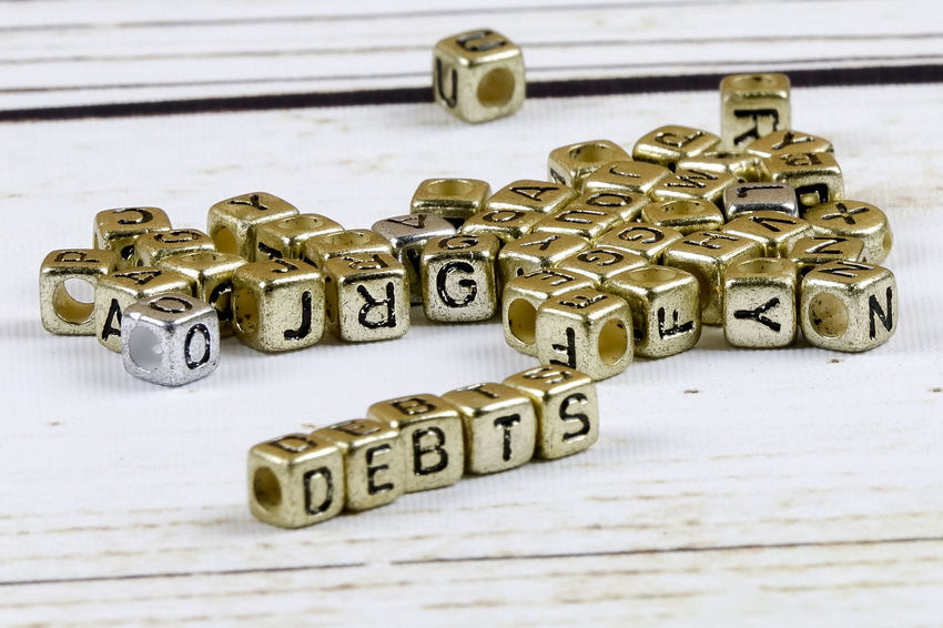 DEBT CONCEPT WITH GOLD DICE ON A WOODEN TABLE Close-up Communication Credit Card Debt Crisis High Angle View Indoors  Key Large Group Of Objects Metal No People Number Selective Focus Shape Still Life Studio Shot Table Text Toy Toy Block Western Script White Background Wood - Material