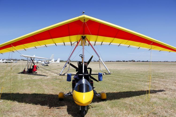 A powered micro light aircraft on the airfield in Australia, waiting for a flight Aerospace Industry Air Vehicle Aircraft Airfield Airplane Aviation Clear Sky Day Flight Flying Machine Grass Hang Glider Hanging Microlight Multi Colored Nature No People Outdoors Powered Flight Sky Transportation