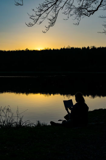 Reading women at sunset Backlight Beauty In Nature Lake One Person One Woman Only Reflection Silhouette Sunset Sunset Silhouettes Tranquility Water
