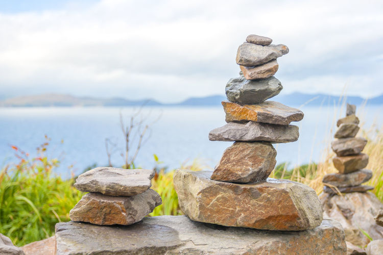 Pile of stones in front of the beach Stack Rock Solid Stone - Object Rock - Object Balance Nature Zen-like Sky Focus On Foreground Water No People Tranquility Day Stone Cloud - Sky Land Sea Beauty In Nature Outdoors Pebble