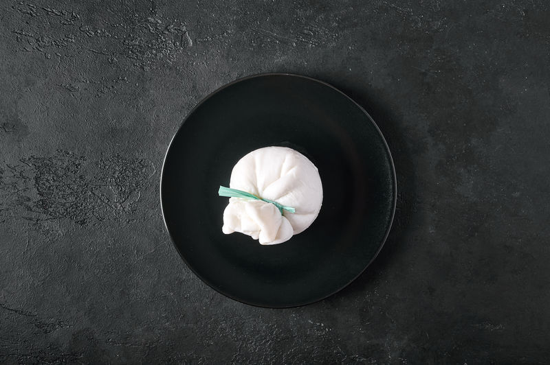 Traditional italian burrata cheese on dark plate on graphite background. top view, copy space