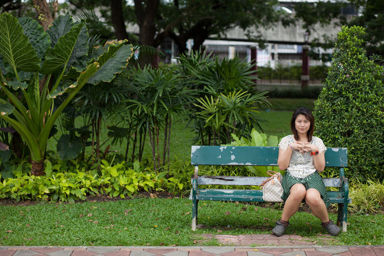 Portrait of smiling woman sitting in park