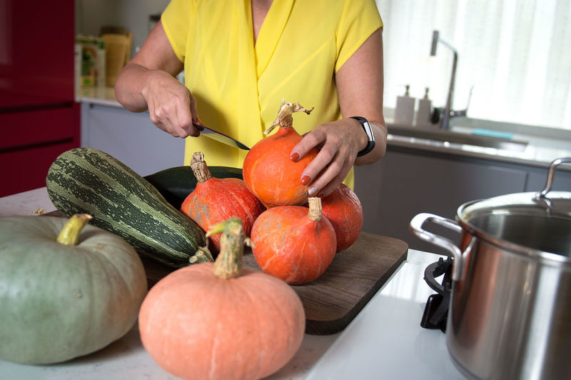 Kitchen setting - woman preparing pumpkins, gourds, squash and marrow for pickle Kitchen Domestic Kitchen Food And Drink Domestic Room Food Home Healthy Eating Wellbeing Household Equipment Freshness Indoors  One Person Preparation  Vegetable Fruit Lifestyles Domestic Life Kitchen Utensil Midsection Preparing Food Pumpkin Squash Pickle Gourds Marrow Moms & Dads