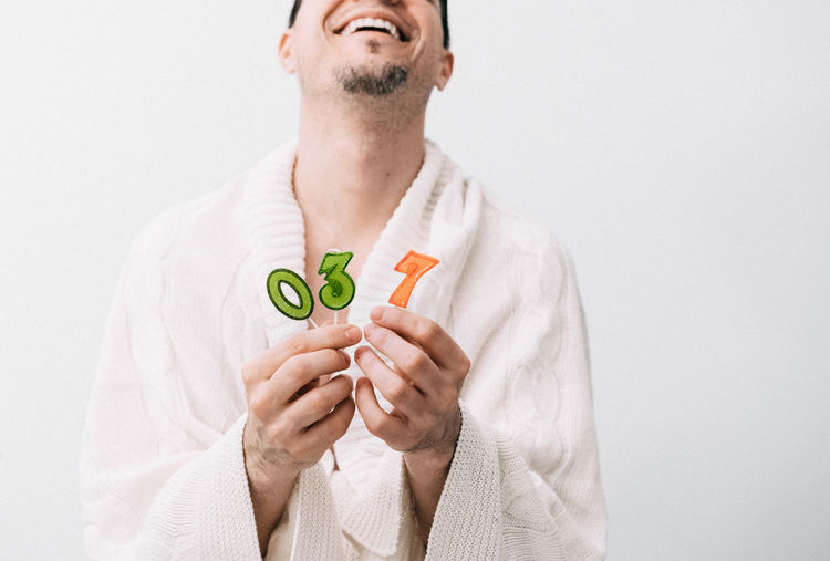 Midsection Of Man Wearing Bathrobe While Holding Birthday Candles Against White Background