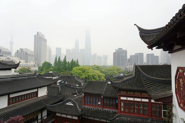 View of roofed structures with tall buildings in distant
