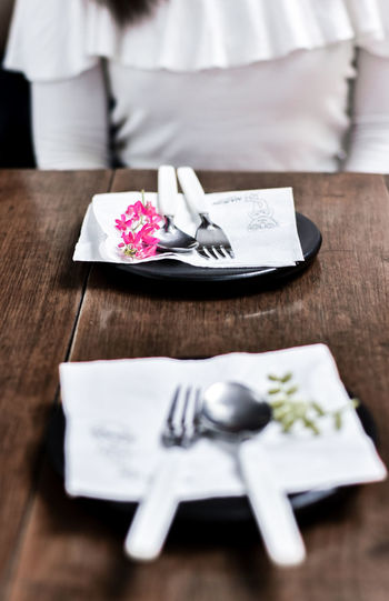 Midsection Of Woman Sitting By Table With Plate