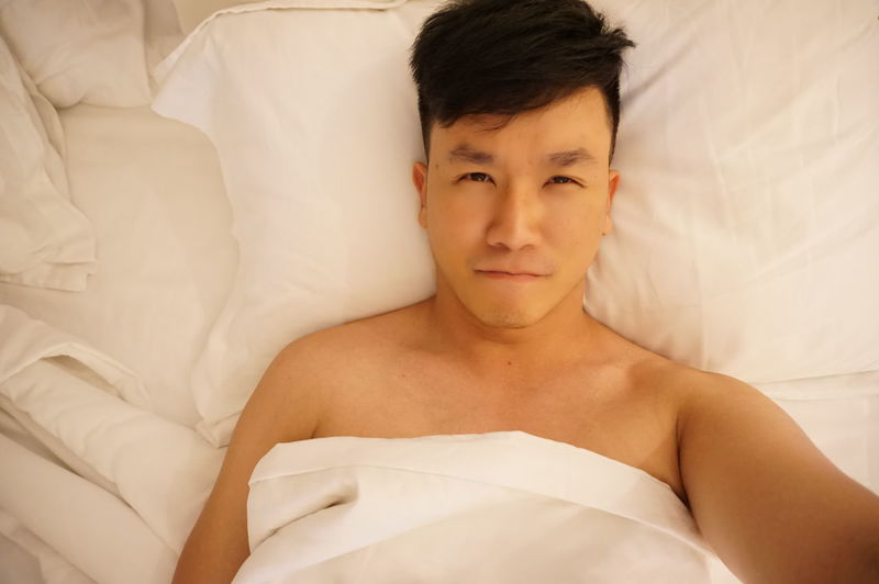 Directly above portrait of shirtless young man lying on bed