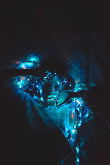High angle view of woman holding illuminated light while lying on bed