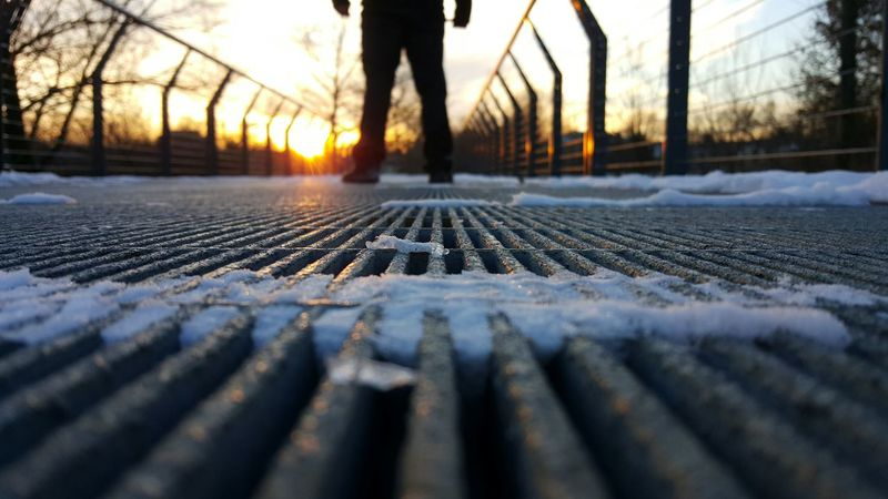 Sunset Outdoors Nature Surface Level Sunlight Autumn Tree Day Close-up Beauty In Nature Human Body Part People Winter Urban Nature Legs Non Recognizable Person Strength Standing Steel Bridge Low Angle View Winter Sunset Bare Trees Converging Lines Light Snow Focus Of Foreground