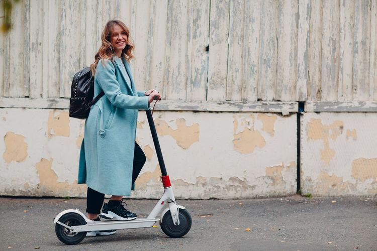 Full length of woman standing on push scooter