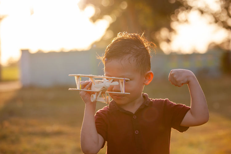 Portrait of boy holding toy airplane at park