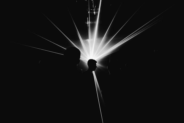 Silhouette people against illuminated lights at night