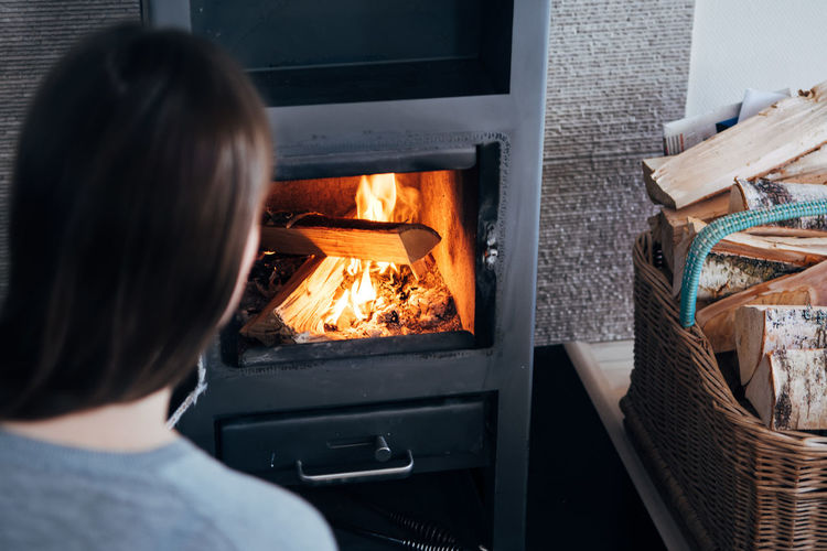 Rear View Of Woman By Fireplace At Home
