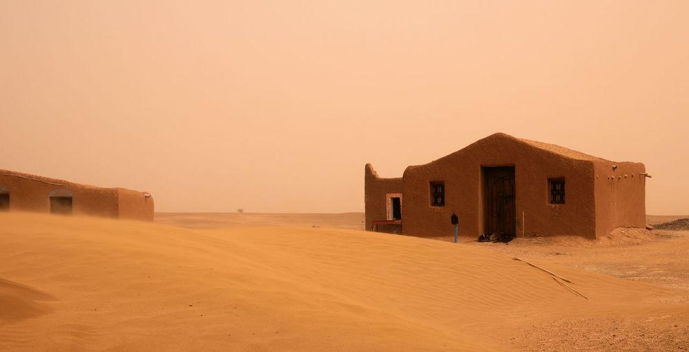 Houses on desert against clear sky during sunset
