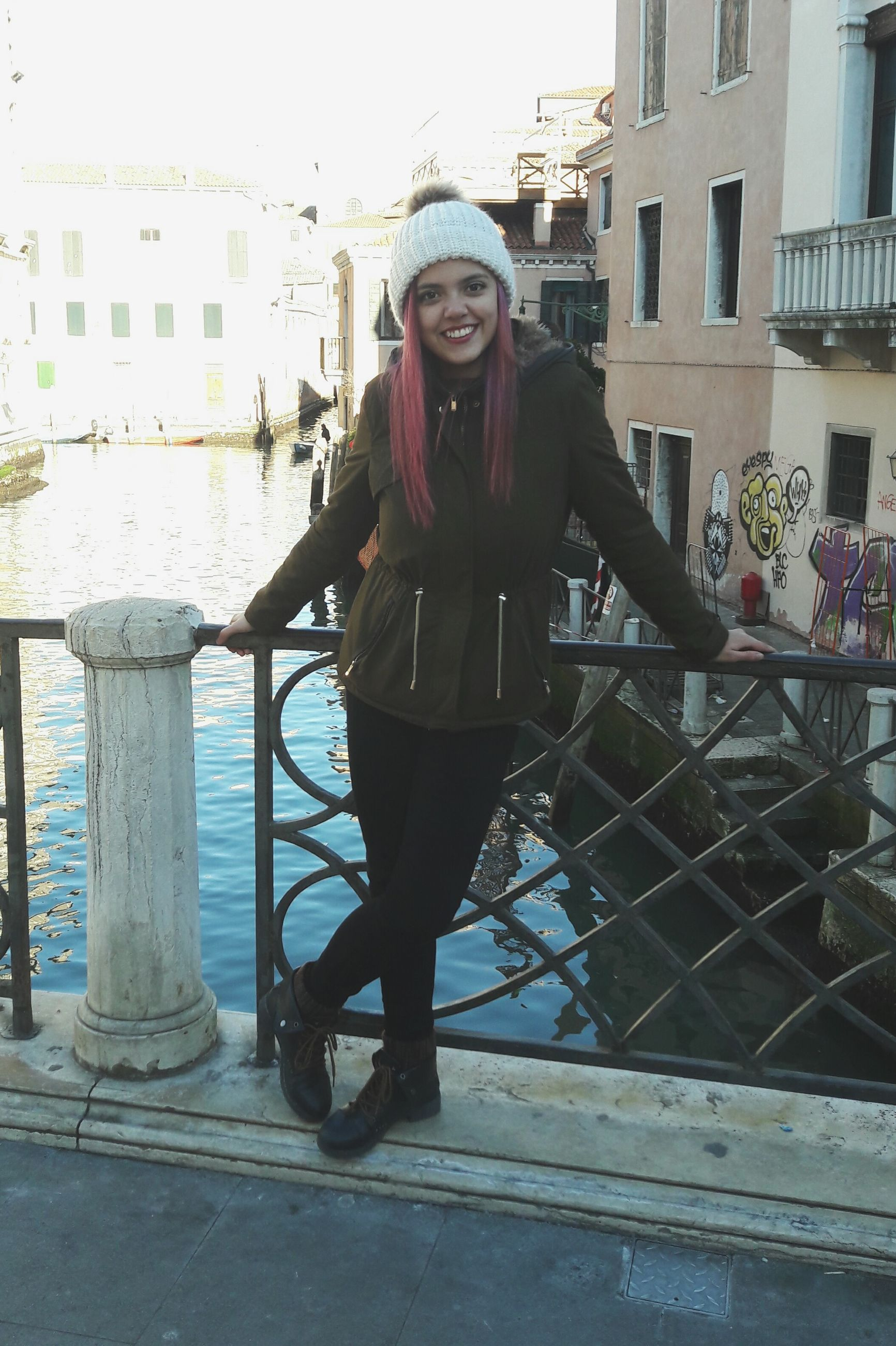 full length, looking at camera, one person, lifestyles, portrait, real people, warm clothing, leisure activity, knit hat, outdoors, happiness, front view, day, young women, city, built structure, building exterior, architecture, smiling, sky, one woman only, water, young adult, adults only, people, adult
