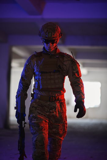 Portrait of soldier standing in illuminated room