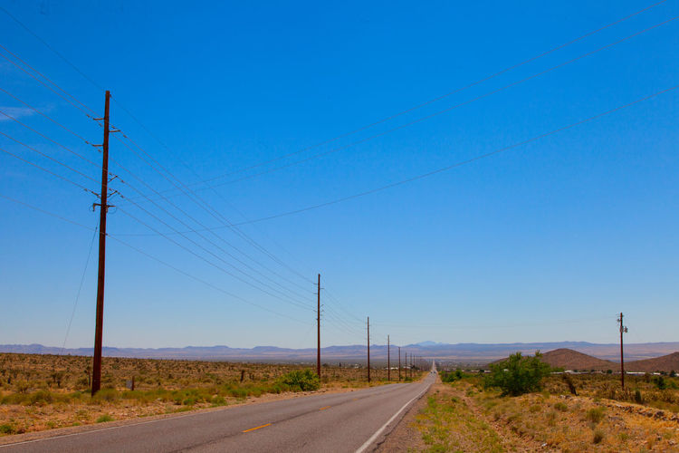Road in dry dessert landscape Blue Cable Clear Sky Connection Day Electricity  Electricity Pylon Fuel And Power Generation Landscape Nature No People Outdoors Power Line  Power Supply Road Scenics Sky Technology Telephone Line The Way Forward Transportation Tree