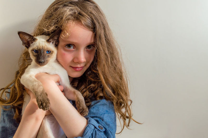 Portrait of smiling young woman with cat